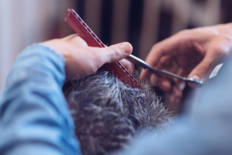 Red comb being used by a barber stock image