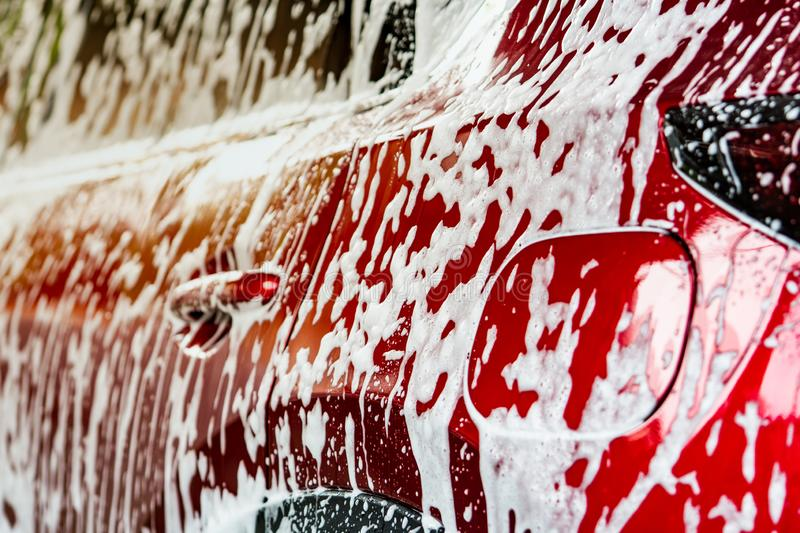 Red compact SUV car with sport and modern design washing with soap. Car covered with white foam. Car care service business concept stock photos
