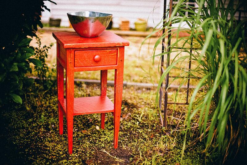 Red console table in garden stock photography