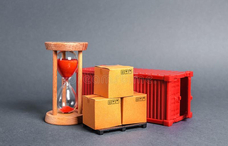 Red container with cardboard boxes and an hourglass. Express delivery in short time concept. Temporary storage, limited offer. And discount. Optimization of royalty free stock photos