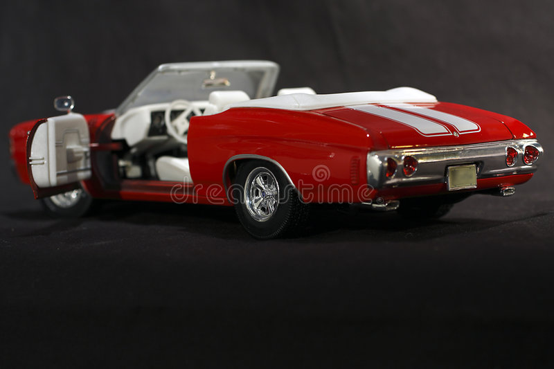 Red Convertible Sports Car. Bright red convertible sports car is a scale model of a Chevrolet Chevelle SS. Focus is on the driver's side with door open. Image royalty free stock image
