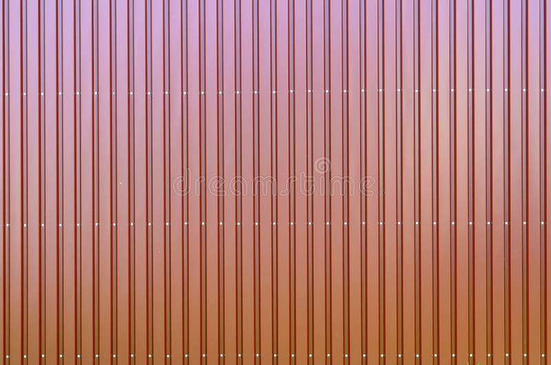 Red corrugated galvanised iron cladding. Colorful red corrugated galvanised iron cladding on a wall or fence in a full frame background architectural texture royalty free stock images