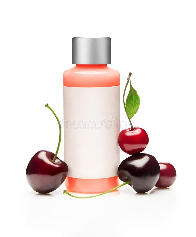 Red cosmetic bottle with cherry royalty free stock images