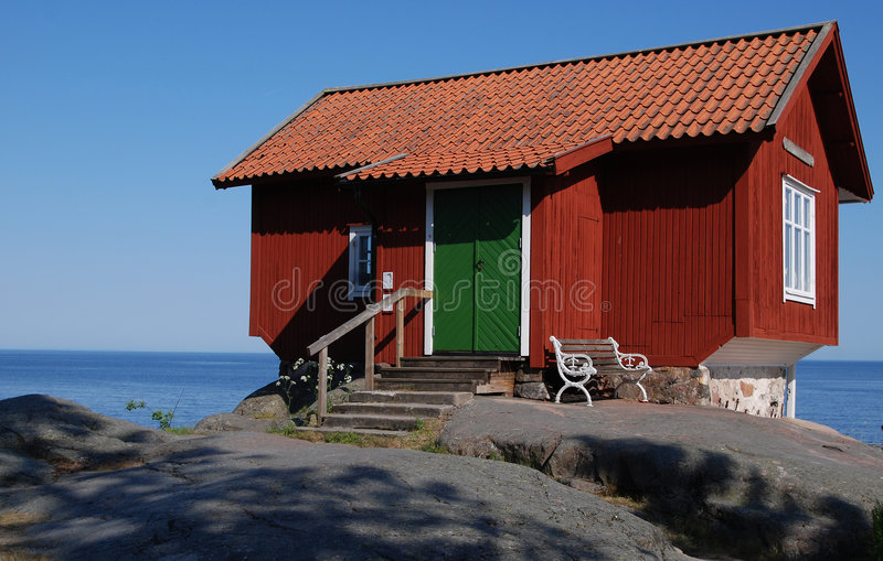 Red cottage by sea