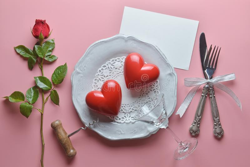 Red couple heart, wine opener, cocktail glass on white dish, with fork and knife in ribbon, Rose , On pink background. royalty free stock images