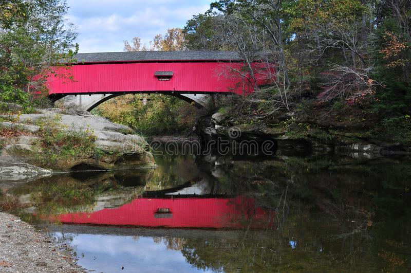 Red Covered Bridge in Indiana. This covered bridge spans a river in Indiana`s Turkey Run Park. Early fall mixes leaves and colors on the trees stock image
