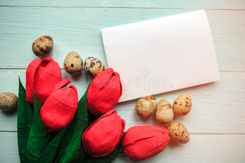 Red craft tulips, quail eggs and white mockup blank on wooden background, top view. Easter concept royalty free stock photos