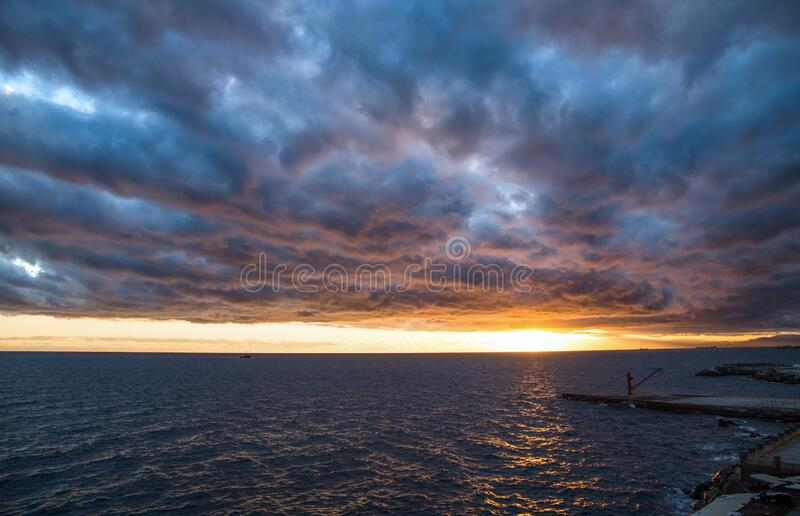 The red crane on the pier under a cloudy sky at sunset royalty free stock photography