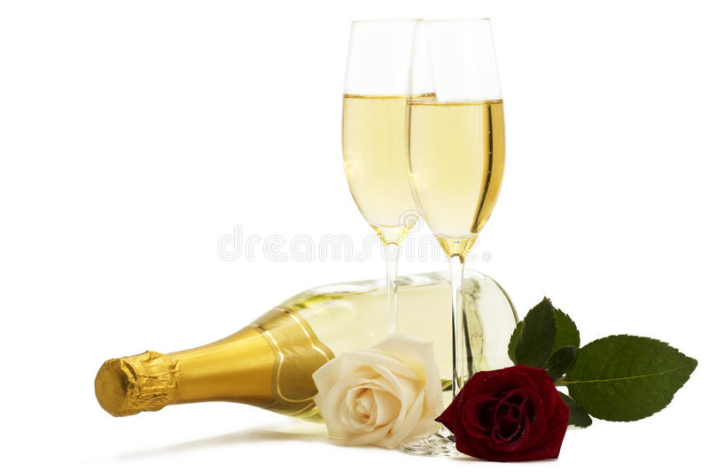 Red and cream-colored roses with two champagne gla royalty free stock images