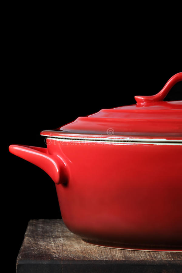 Red Crock Pot. Or casserole dish, on kitchen board, over black background royalty free stock photo