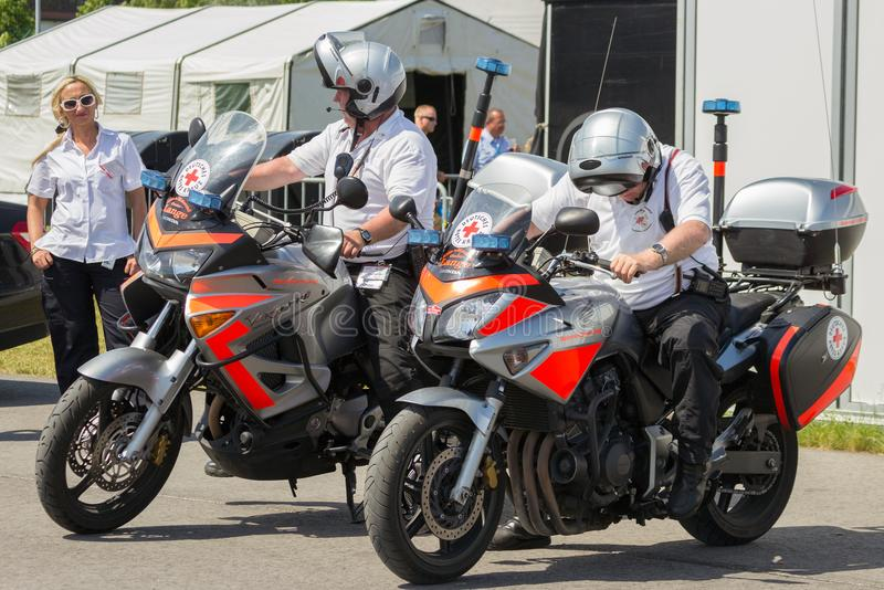 Red cross medical motor bikes. BERLIN - JUL 11, 2013: German red cross Deutsches Rotes Kreuz motor bikes and personnel during the ILA event royalty free stock image