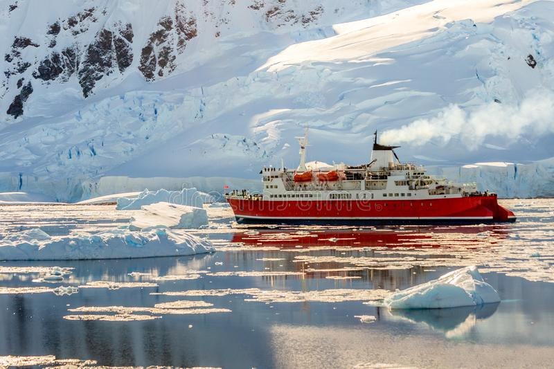 Red cruise steamboat drifting among the icebergs with huge rock and glacier in background, Neco bay, Antarctica. Area, blue, bow, climate, cold, deck stock photos