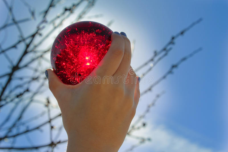 Red Crystal Ball. Held up by a young girl blocked by the sun and shining through royalty free stock image