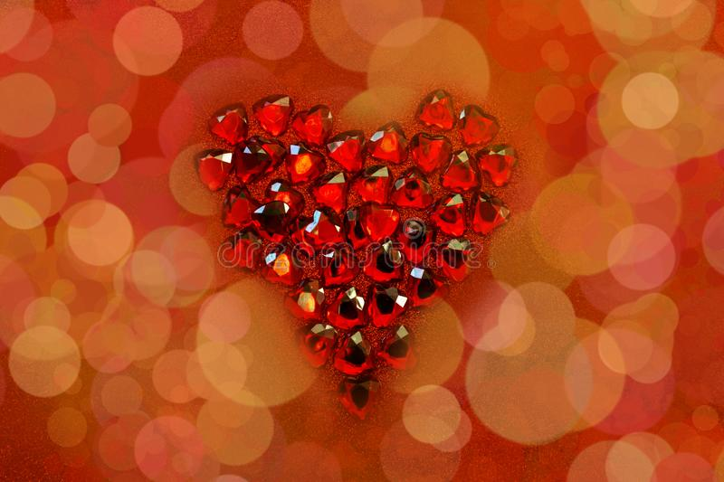 Red crystal hearts with a heart form on red glitter background. St. Valentine`s day greetings postcard. Lover`s day. Love. Red crystal hearts with a heart form royalty free stock image