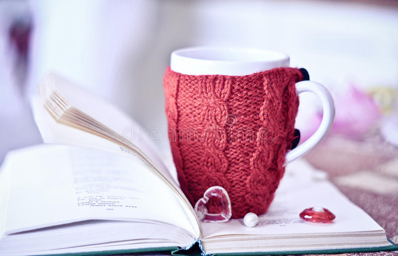 Red cup on the book with sweater stock images