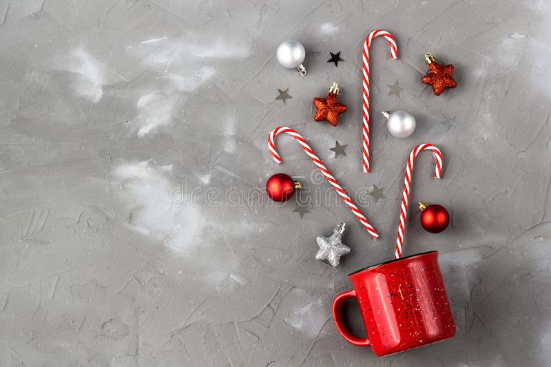 Red cup with candy cane, ball and stars on grey background. Christmas and new year concept. Red cup with candy cane, ball and stars on grey background. Christmas royalty free stock images