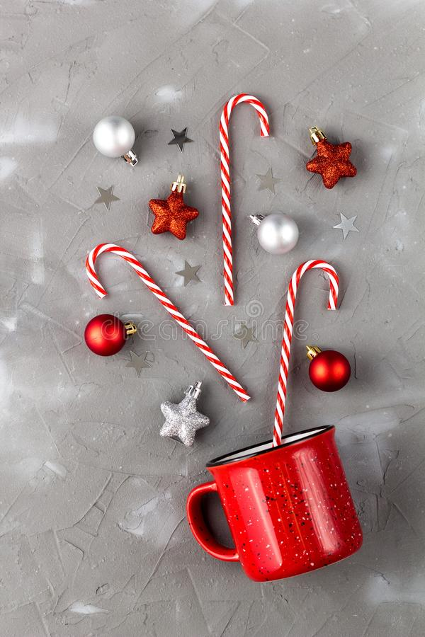Red cup with candy cane, ball and stars on grey background. Christmas and new year concept. Red cup with candy cane, ball and stars on grey background. Christmas stock images