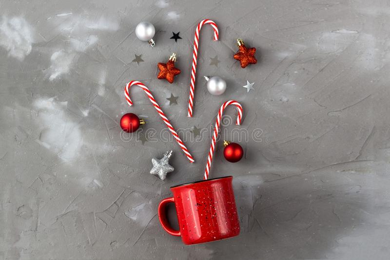 Red cup with candy cane, ball and stars on grey background. Christmas and new year concept. Red cup with candy cane, ball and stars on grey background. Christmas royalty free stock image