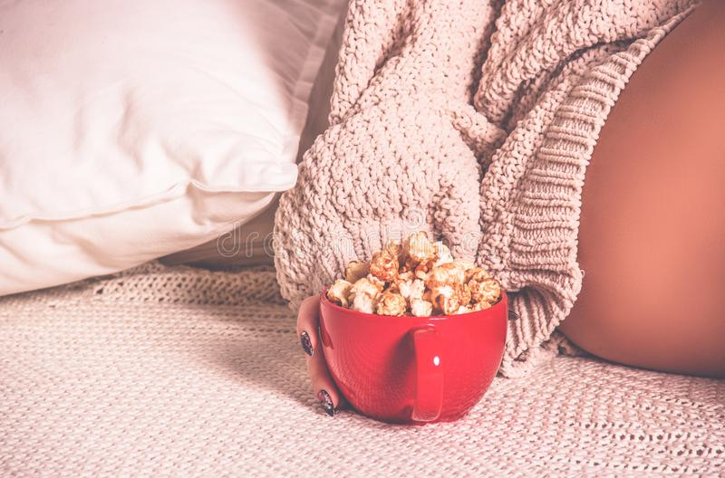 Red cup with caramel popcorn on a knitted plaid. Copy space. Vintage tinting stock image