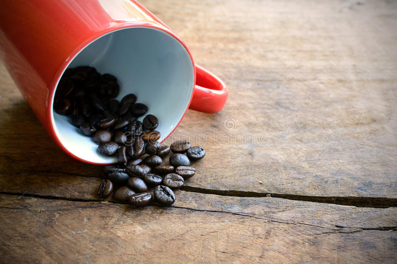 Red cup with coffee beans on wooden table. Red cup with coffee bean on old wooden table stock photography