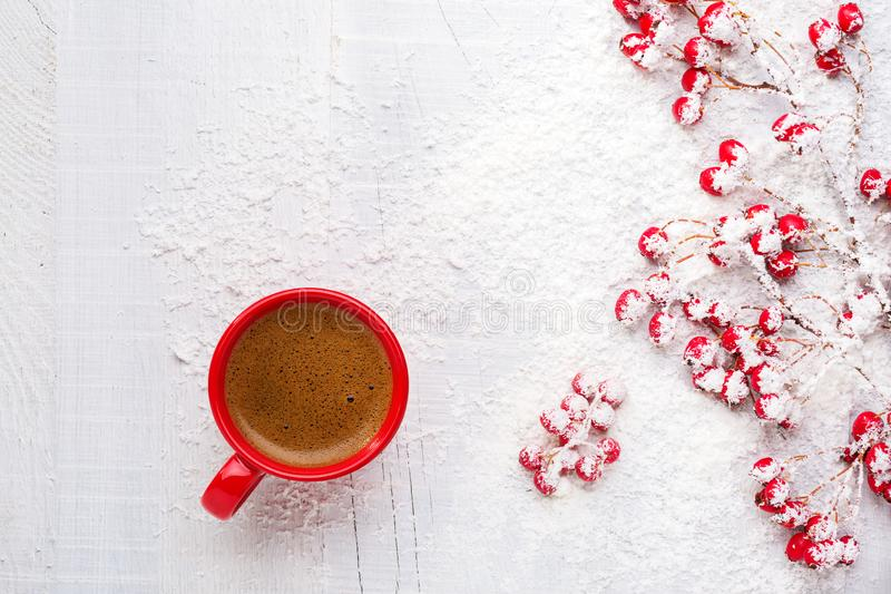 Red cup of coffee and branches with hawthorn berries on an old white wooden background. Flat lay stock photo