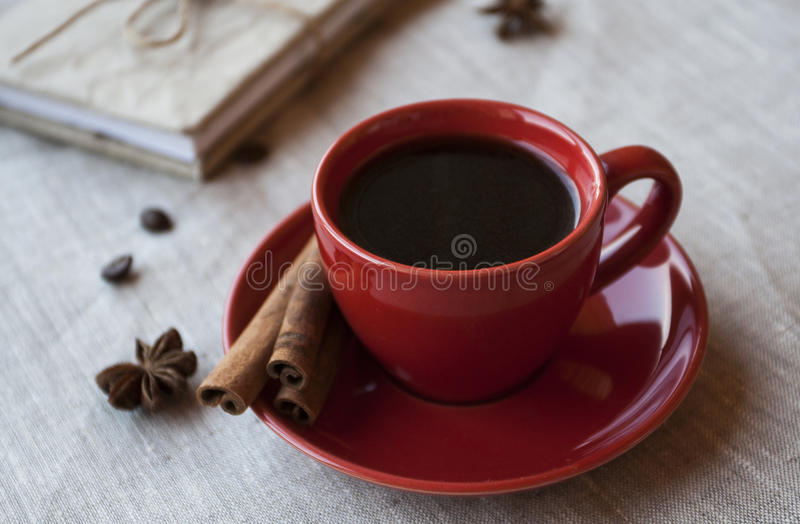 Red cup of coffee with coffee beans and spices cinnamon royalty free stock photography