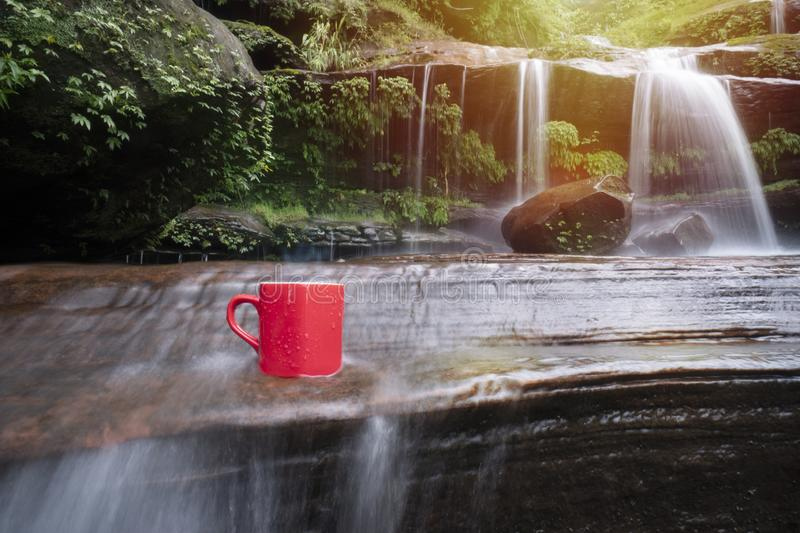 Red cup of coffee with waterfall nature background stock photo