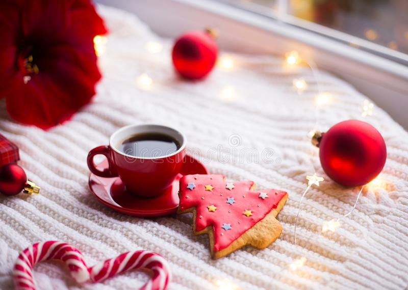Red cup with espresso coffee and gingerbread in form of fir on white knitted plaid surrounded with winter decor. Amaryllis, red Christmas balls, gift box and royalty free stock photo