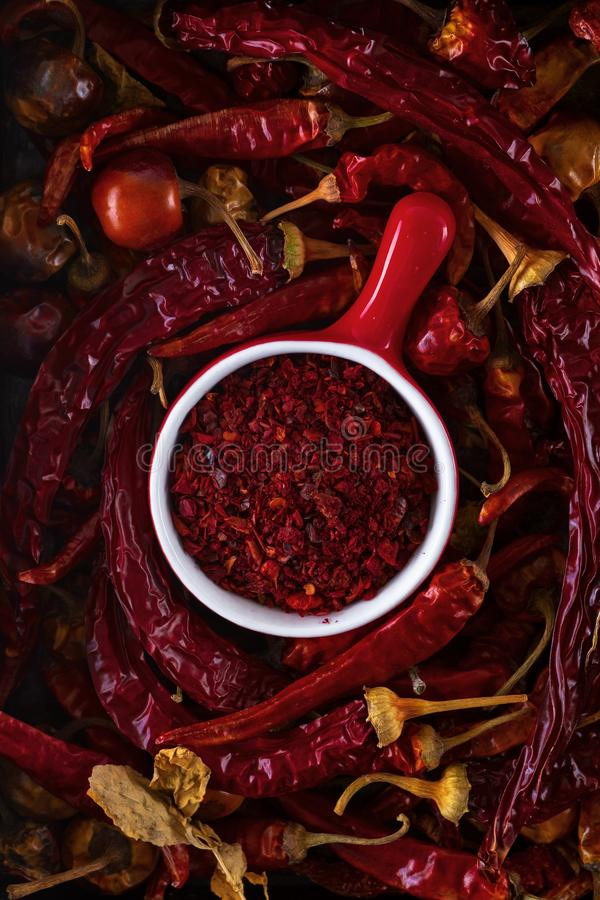 Red cup with ground red pepper surrounded by dry pods of red pepper, top view, closeup stock images