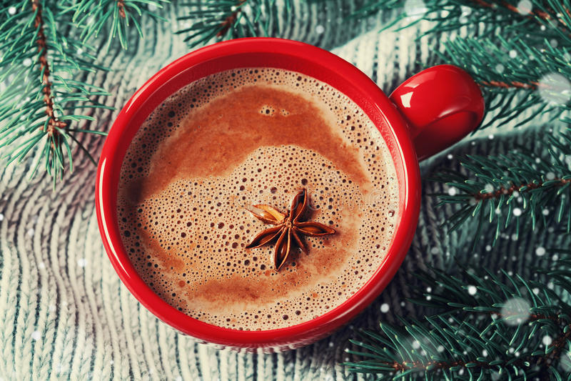 Red cup of hot cocoa or hot chocolate on knitted background with fir tree, traditional beverage for winter time stock photos