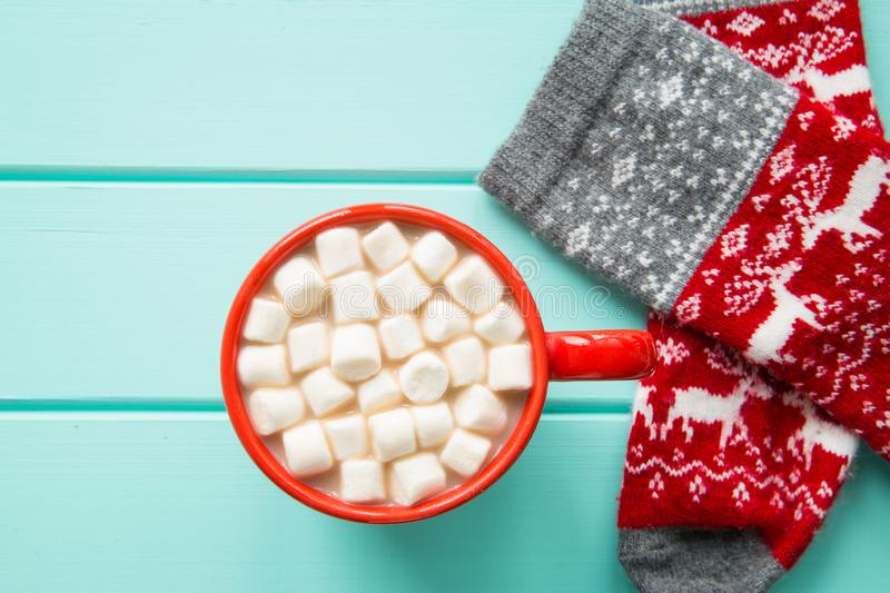 A red cup of hot cocoa, marshmallow and christmas socks on turquoise background. Winter time bright colors stock images