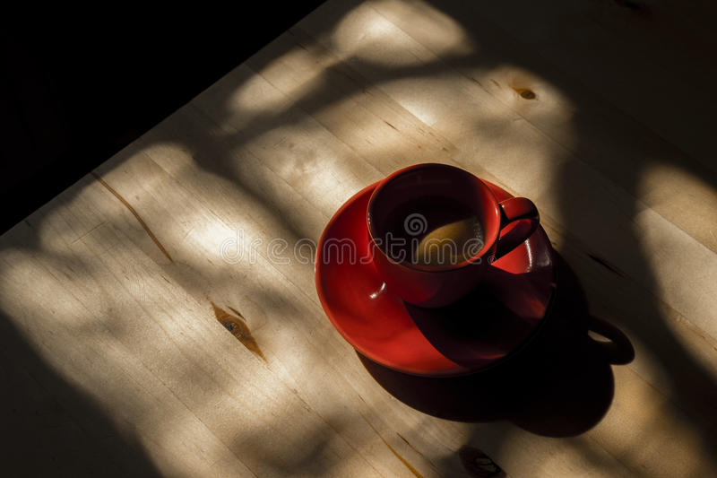 Red Cup and Saucer on Wood Table with Shadows royalty free stock images