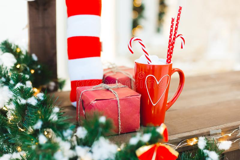Red cup of tea or coffee or hot chokolate with sweets and gift - Christmas Holiday Background royalty free stock photo
