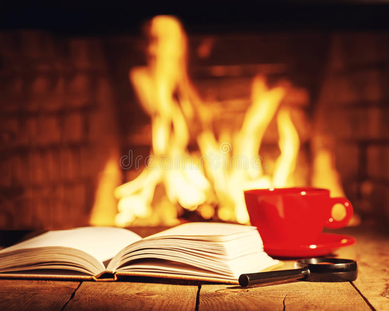 Red cup of tea or coffee, magnifier glass and old books. stock photography