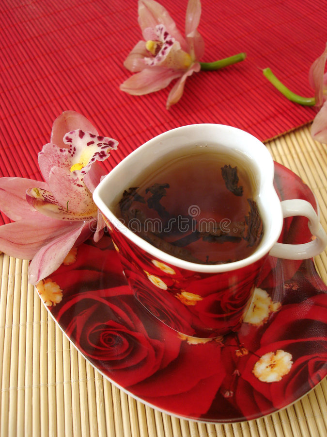 Red cup of tea in the form of heart with pink orchids over straw royalty free stock image