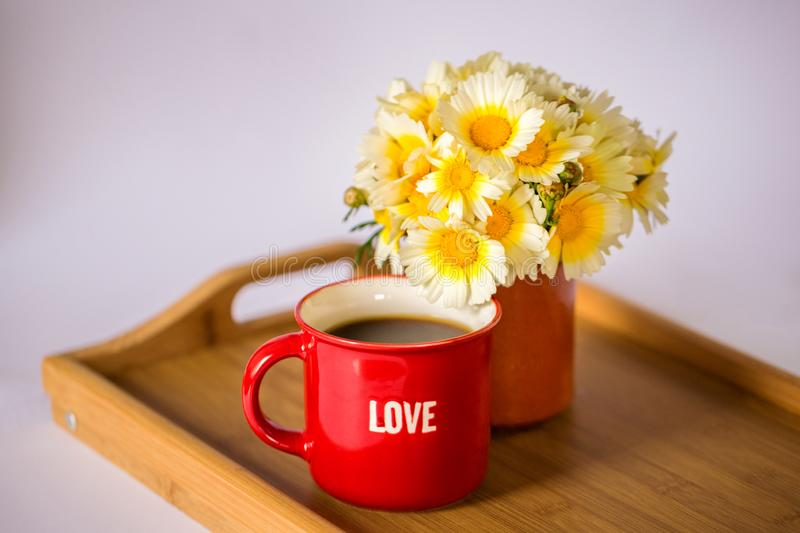 A red cup with the word `love` with hot coffee / tea and a bouquet of daisies on a wooden tray stock images
