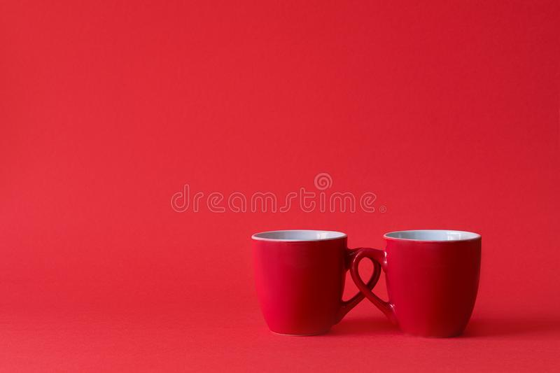 Red cups of tea or coffee on red paper background. Copy space stock image