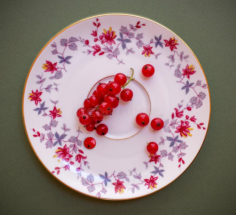 Red currant berries on a porcelain ornamental saucer on a dark background.  Healthy food stock photography