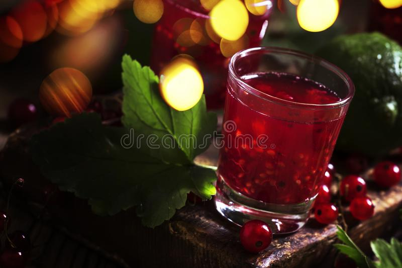 Red currant cocktail with juice, vodka and lime on dark table, top view stock photography