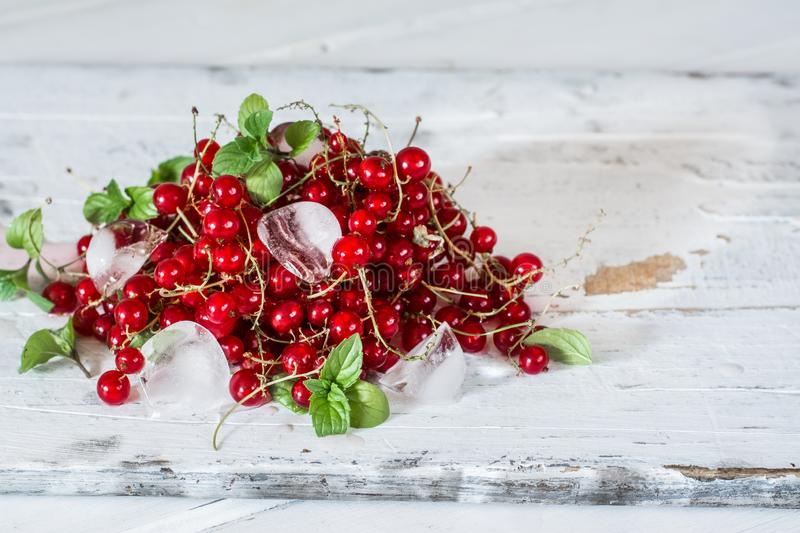 Red currant with ice and green leaves on white wooden background. Still life of food. Cubes of ice with berries. Red currant with ice and green leaves on white stock photo