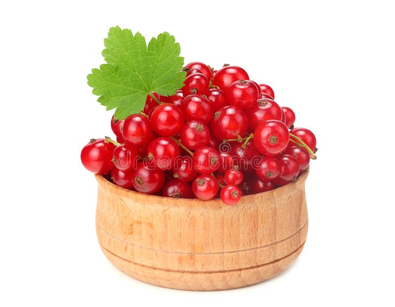 Red currant in wooden bowl with green leaf isolated on white background. healthy food stock image