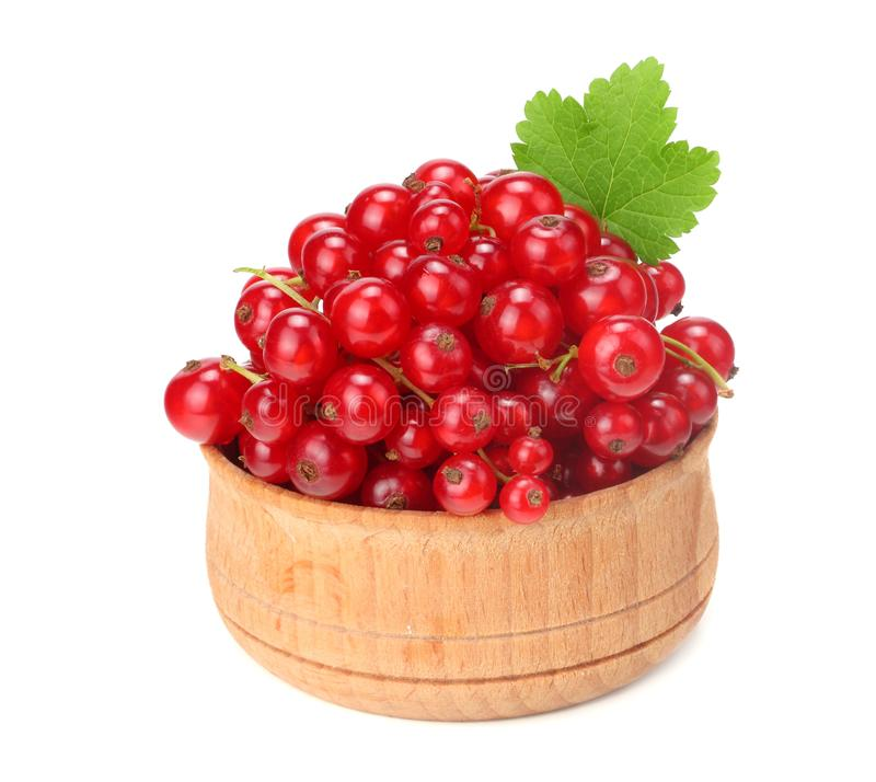 Red currant in wooden bowl with green leaf isolated on white background. healthy food royalty free stock image