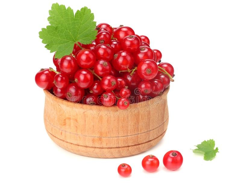 Red currant in wooden bowl with green leaf isolated on white background. healthy food stock photography