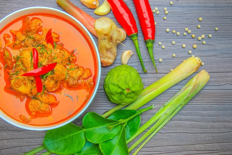 Red curry chicken, Thai Spicy food and fresh herb ingredients on. Wooden top view/still life, selective focus royalty free stock photography