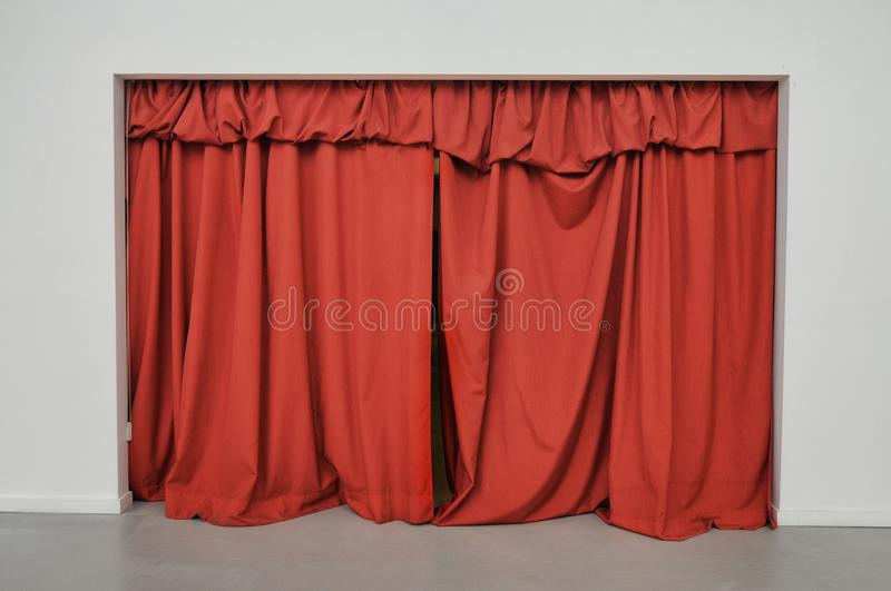 Red curtain closed over large doorway on a white wall stock images