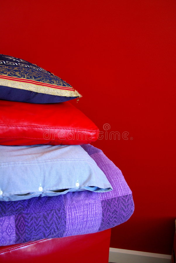 Red Cushions & Wall. Photograph taken featuring stacked cushions and pillows in front of a red feature wall in a suburban home (Adelaide, South Australia royalty free stock image