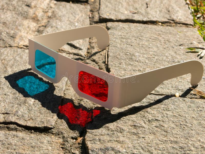 Red cyan stereophotography anaglyph 3D glasses on rocks ground pattern royalty free stock photos