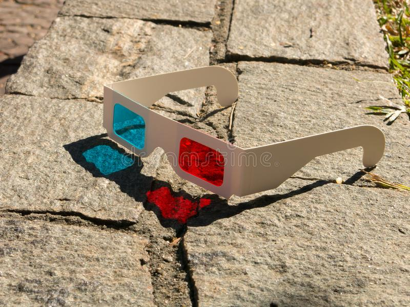 Red cyan stereophotography anaglyph 3D glasses on rocks ground pattern royalty free stock images