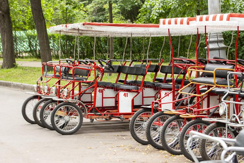 Red cyclo velomobiles with a canopy for the whole family. Parked rental tourist trike vehicles. Ecological transport for walking royalty free stock photo