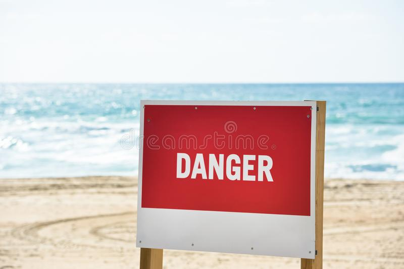 Red danger sign on an ocean beach. With waves on the background. Strong current danger concept stock images
